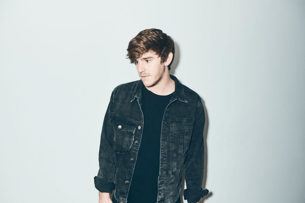 nghtmre wearing a jean jacket posing in front of a wall