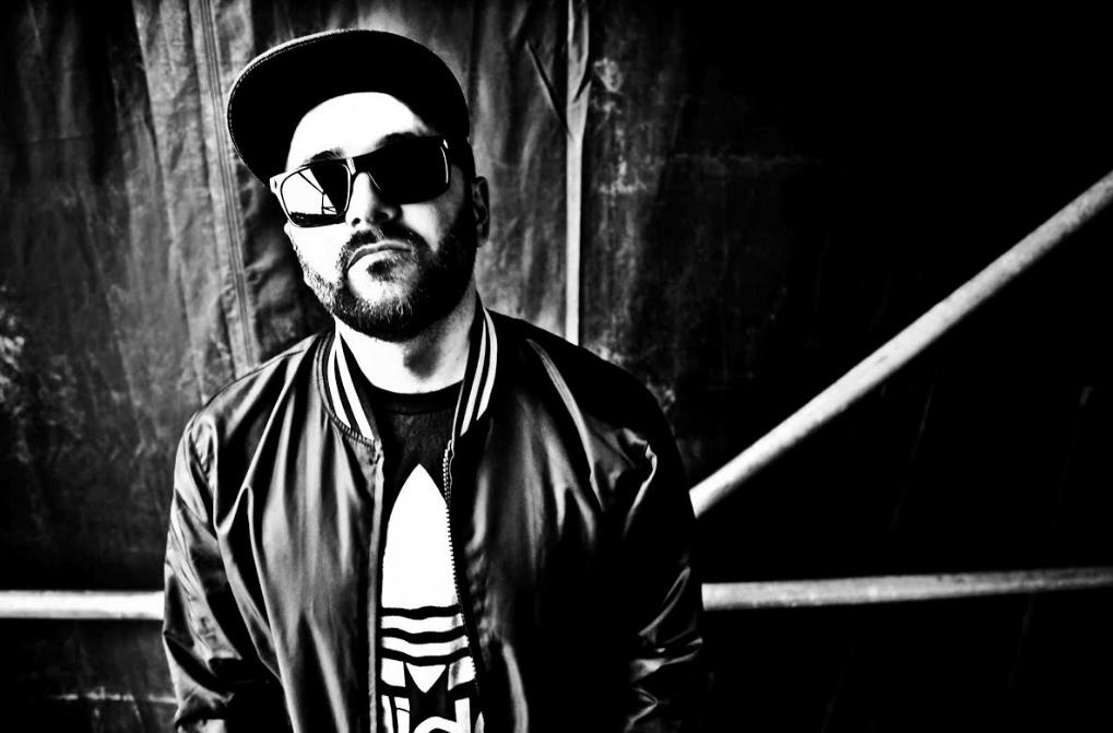black and white photo of dj Gramatik wearing sunglasses and Adidas jacket and shirt